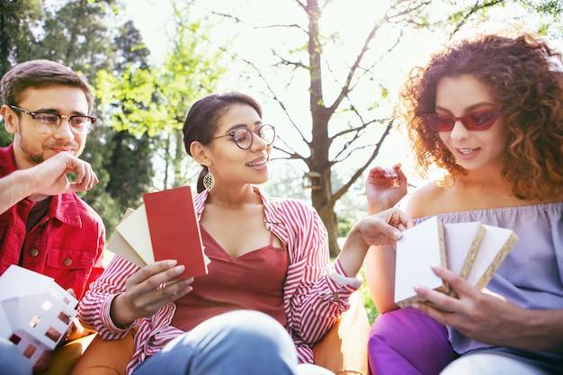 Día impresionante. encantada mujer morena sentada al aire libre con sus compañeros de trabajo y discutiendo su puesta en marcha