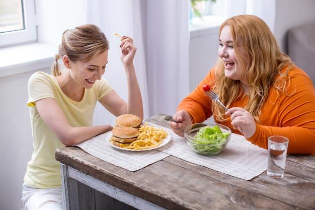 Día increíble. riendo a mujer delgada comiendo comida rápida y hablando con su amigo gordo comiendo una ensalada