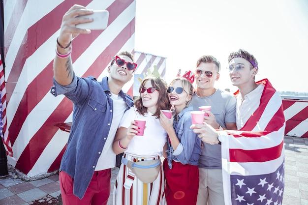 Día de la independencia. gente alegre sosteniendo vasos de papel mientras mira el teléfono