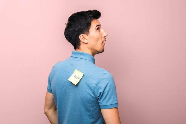 Día de los inocentes. hombre de aspecto tonto en polo azul con una nota adhesiva amarilla con la palabra tonto en la espalda mirando estúpidamente contra rosa