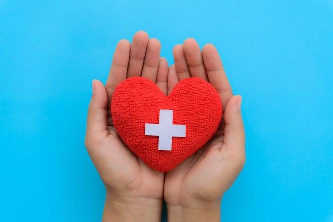 Día internacional de las enfermeras, mano de mujer sosteniendo corazón rojo sobre fondo azul.