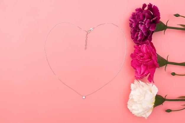 Día internacional de la mujer con flores y collar con forma de corazón sobre fondo rosa