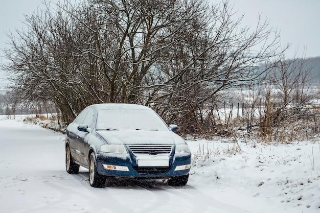 Día de invierno, un auto cubierto de nieve no puede ir por el clima_
