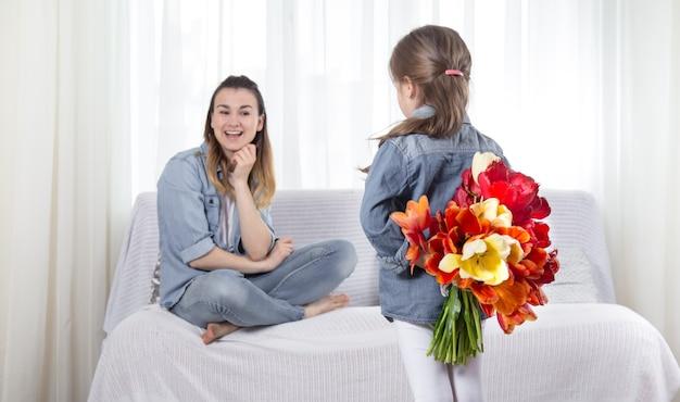 Día de la madre. hijita con flores felicita a su madre