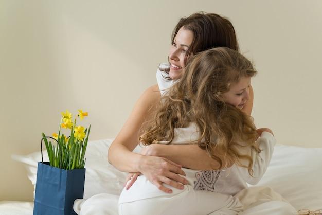 Día de la madre. la madre abraza a su pequeña hija.