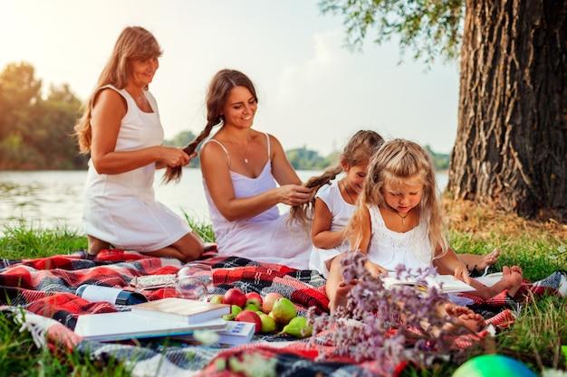 Día de la madre. madre, abuela y niños tejiendo trenzas de pelo entre sí. familia divirtiéndose durante el picnic