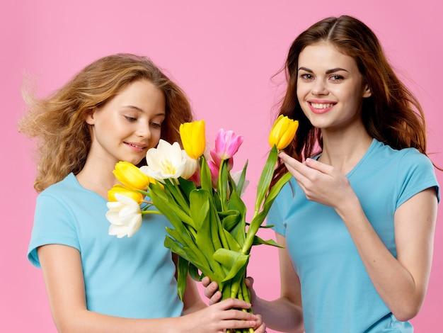 El día de la madre, una mujer joven con un niño posando con flores, un regalo para el día de la mujer y el día de la madre