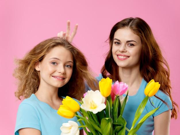 El día de la madre, una mujer joven con un niño que presenta un espacio con flores, un regalo para el día de la mujer y el día de la madre