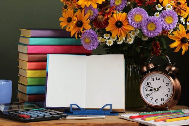 Día del maestro, 1 de septiembre. regreso a la escuela. un ramo de flores de otoño, un reloj despertador y un libro abierto sobre un soporte.