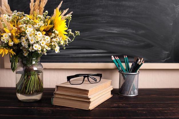 Día del maestro. pizarra negra y flores silvestres frescas en florero