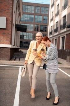 Dia maravilloso. dos mujeres empresarias riendo en elegantes chaquetas y pantalones de pie al aire libre frente a un edificio de oficinas