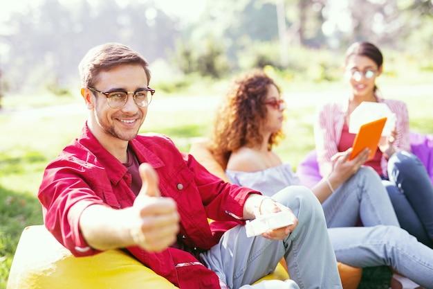 Dia maravilloso. hombre alegre guapo sonriendo y trabajando con sus colegas al aire libre