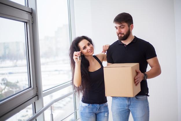 Día de la mudanza. feliz pareja joven llevando cajas.