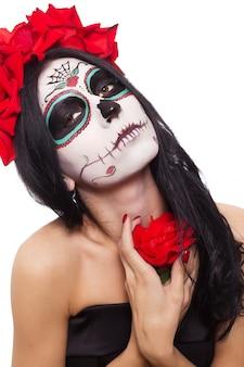 Dia de los muertos. festividad de todos los santos. mujer joven en el día de los muertos máscara cráneo cara arte y rosa. aislado en blanco de cerca.