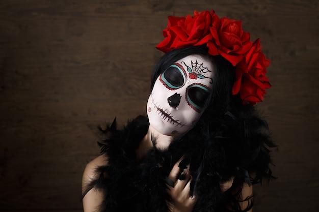 Dia de los muertos. festividad de todos los santos. mujer joven en el día de los muertos máscara cráneo cara arte y rosa. fondo oscuro