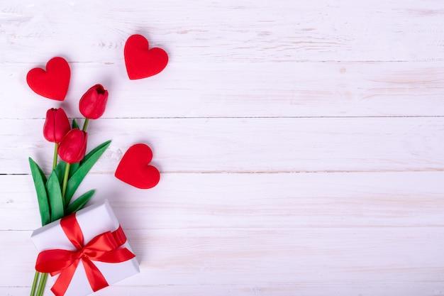 Día de la mujer, día de la madre, concepto del día de san valentín. ramo de tulipanes rojos y un regalo.