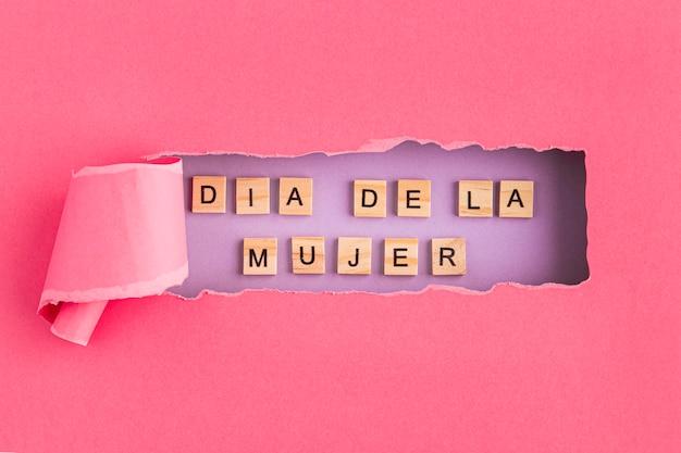 Día de la mujer escrito en español en papel rasgado