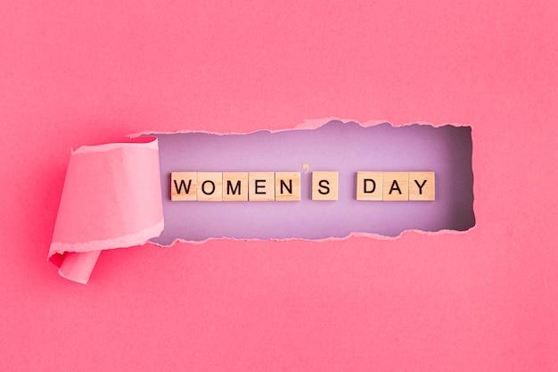 Día de la mujer escrito en letras de scrabble y papel rasgado.