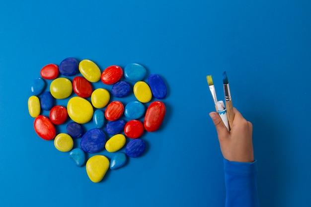 Día mundial del autismo. mano de niño y corazón de piedras sobre fondo azul.