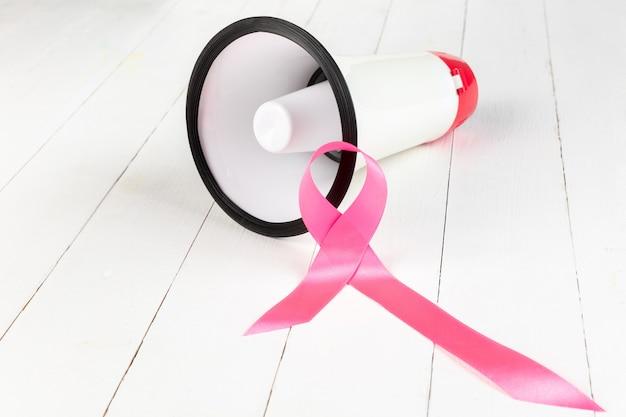 Día mundial del cáncer con cinta rosa y megáfono.