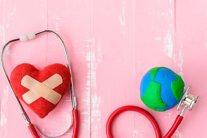 Día mundial de la salud, corazón rojo con estetoscopio sobre fondo de madera rosa.