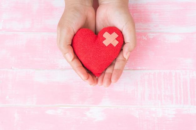 Día mundial de la salud, mano sosteniendo corazón rojo sobre fondo de madera rosa