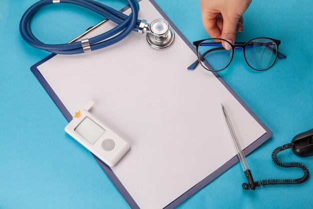 Día mundial de la diabetes. tableta médica con una hoja de papel blanca, glucómetro con una tira de prueba