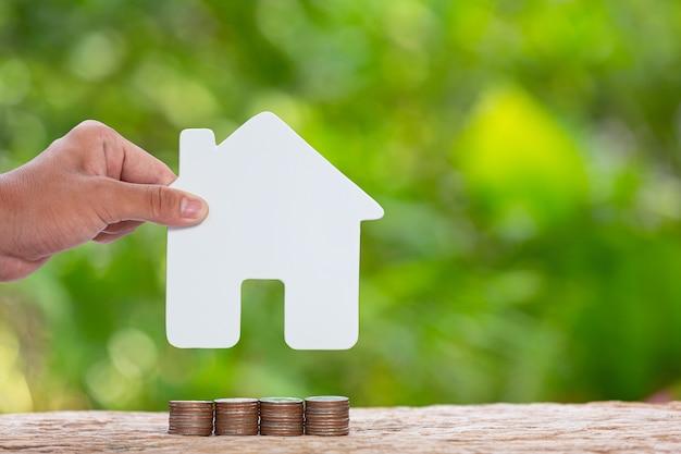 Día mundial del hábitat, imagen de primer plano de un montón de monedas y mano sosteniendo una casa modelo