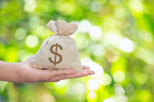Día mundial del hábitat, saco de monedas en la mano