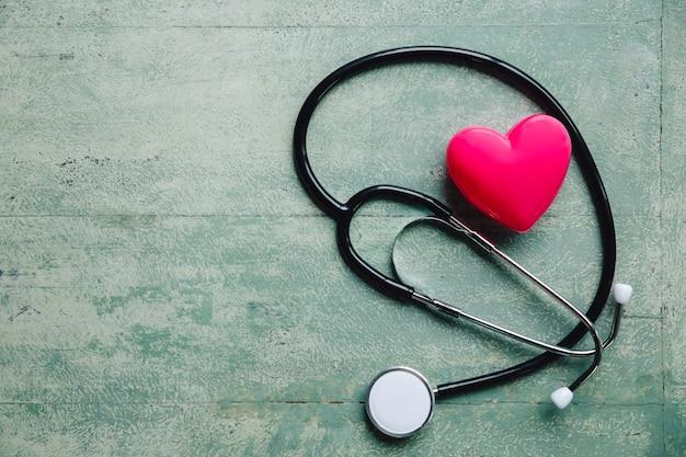 Día mundial de la salud, corazón rojo y estetoscopio en mesa de madera vieja