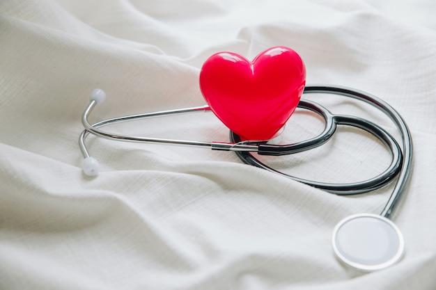 Día mundial de la salud. corazón rojo con estetoscopio sobre tela blanca