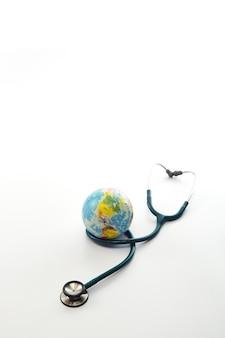 Día mundial de la salud, estetoscopio envuelto alrededor del globo en blanco aislado. salvar al mundo, la atención médica global y el concepto del día de la tierra verde