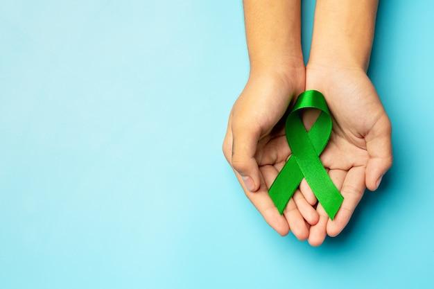 Día mundial de la salud mental. cinta verde puesta en manos del ser humano sobre fondo azul.