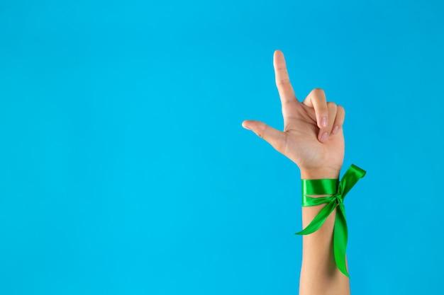 Día mundial de la salud mental. cintas verdes atadas en la muñeca sobre fondo azul.