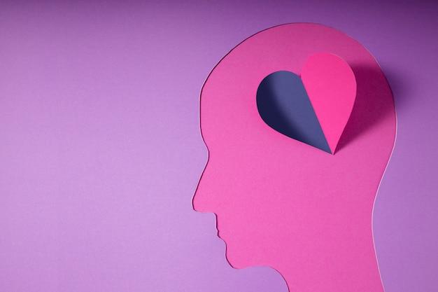 Día mundial de la salud mental. papel cortado como cabeza humana con corazón en lugar del cerebro. psicología