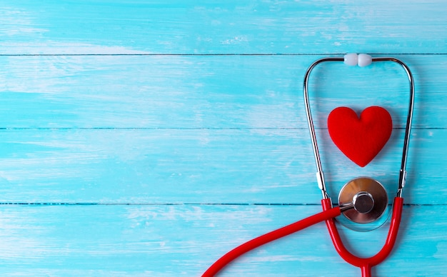 Día mundial de la salud, salud y concepto médico. estetoscopio envuelto alrededor de corazón rojo sobre fondo de madera azul. seguro de salud.