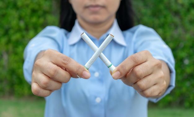 Día mundial sin tabaco. deja de fumar. cerca de la mano de la mujer que sostiene los cigarrillos cruzados.