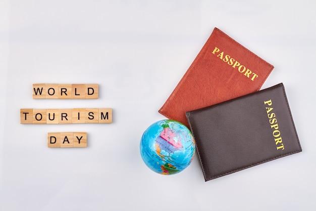 Día mundial del turismo. pasaportes rojos y negros con globo sobre fondo blanco.