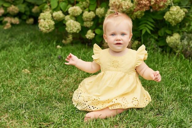 Día del niño, niña niño sobre hierba verde en verano