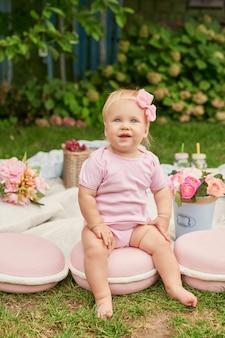 Día del niño, una niña en el parque se sienta en una canasta con macarrones en un picnic de verano