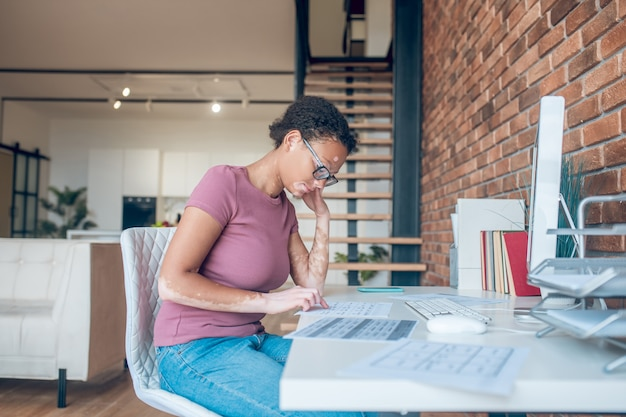 Un día ocupado. una mujer en anteojos trabajando en una computadora y luciendo ocupada