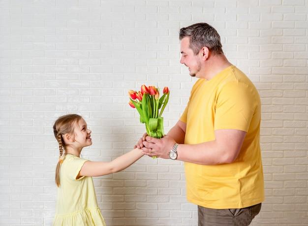Dia del padre. hija feliz de la familia que da a papá las flores