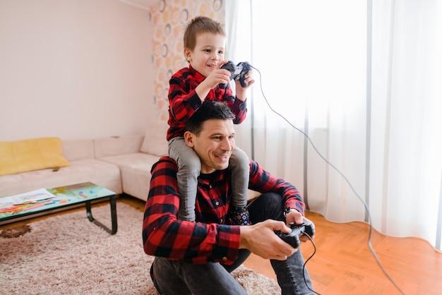Día del padre y el hijo. alegre padre e hijo jugando videojuegos. hijo está sentado sobre los hombros del padre.