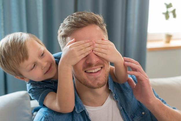 Día del padre hijo cubriendo la cara del padre Foto gratis