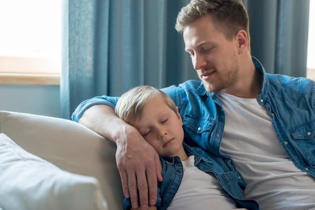Día del padre niño durmiendo en el brazo de papá Foto gratis