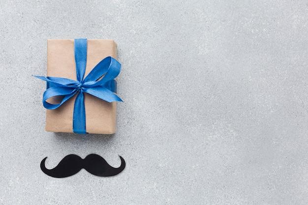 Día del padre con regalo y bigote.