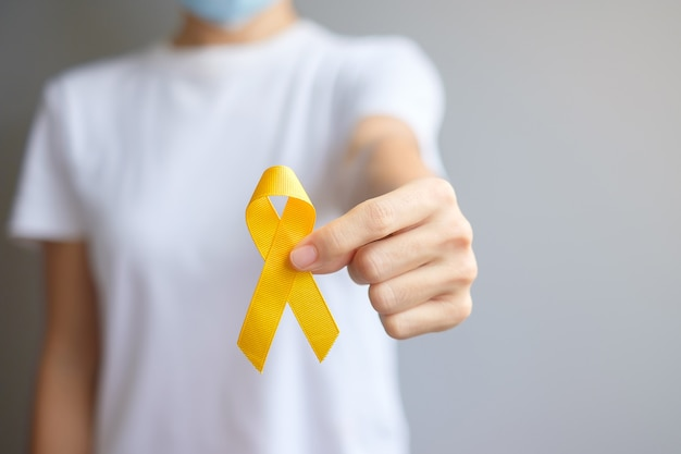 Día de prevención del suicidio, mes de concientización sobre el sarcoma, los huesos, la vejiga y el cáncer infantil, cinta amarilla para apoyar a las personas que viven y están enfermas. concepto de salud infantil y día mundial contra el cáncer.
