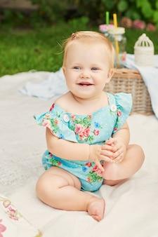 Día de protección infantil, la niña en el parque se sienta en una canasta en un picnic de verano