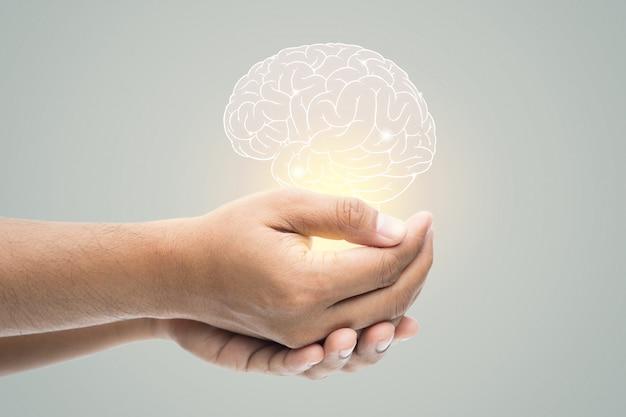Día de la salud mental. hombre que sostiene la ilustración del cerebro en la pared gris