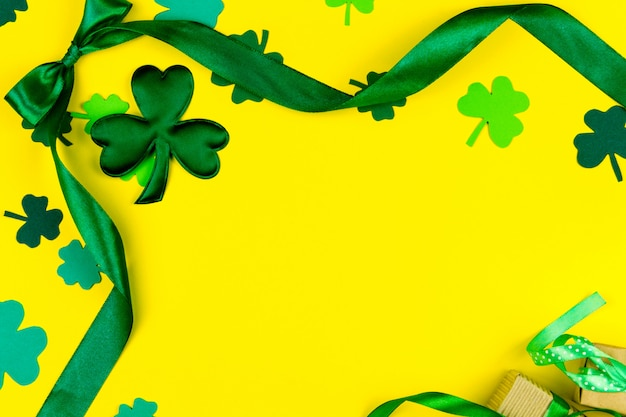 Día de san patricio. cinta curva de diseño verde, tréboles de tres pétalos verdes y caja de regalo sobre fondo amarillo